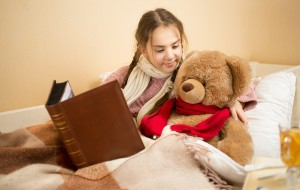 Portrait of cute brunette girl telling story to teddy bear at bed